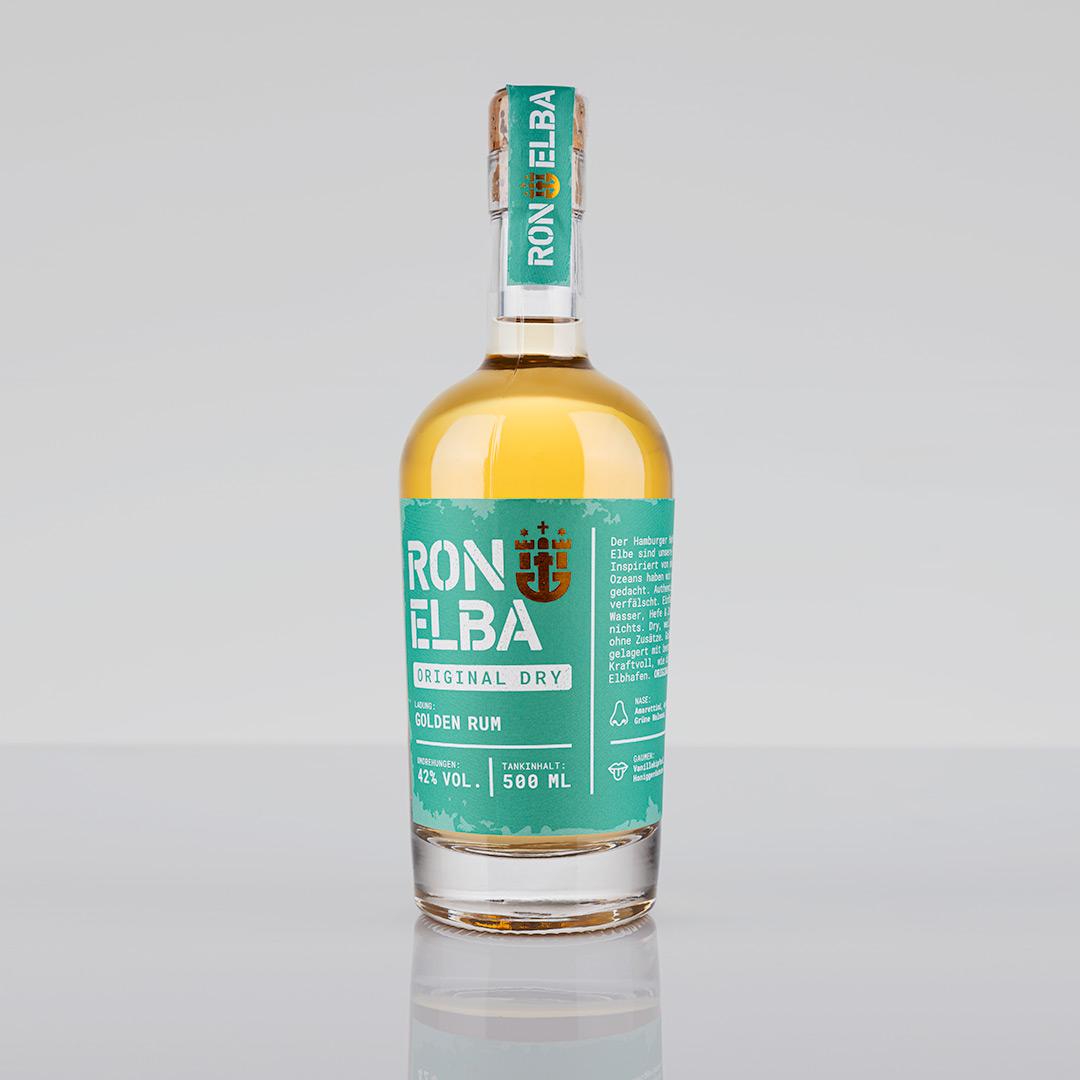 Eine Flasche Golden Rum von Ron Elba vor einem grauen Hintergrund.