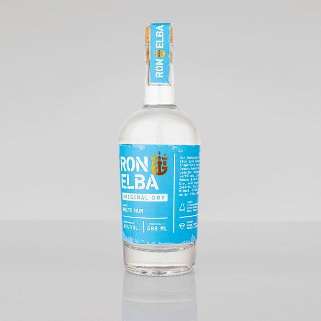 Eine Flasche Ron Elba Rum mit blauem Label. Vor grauem Hintergrund.