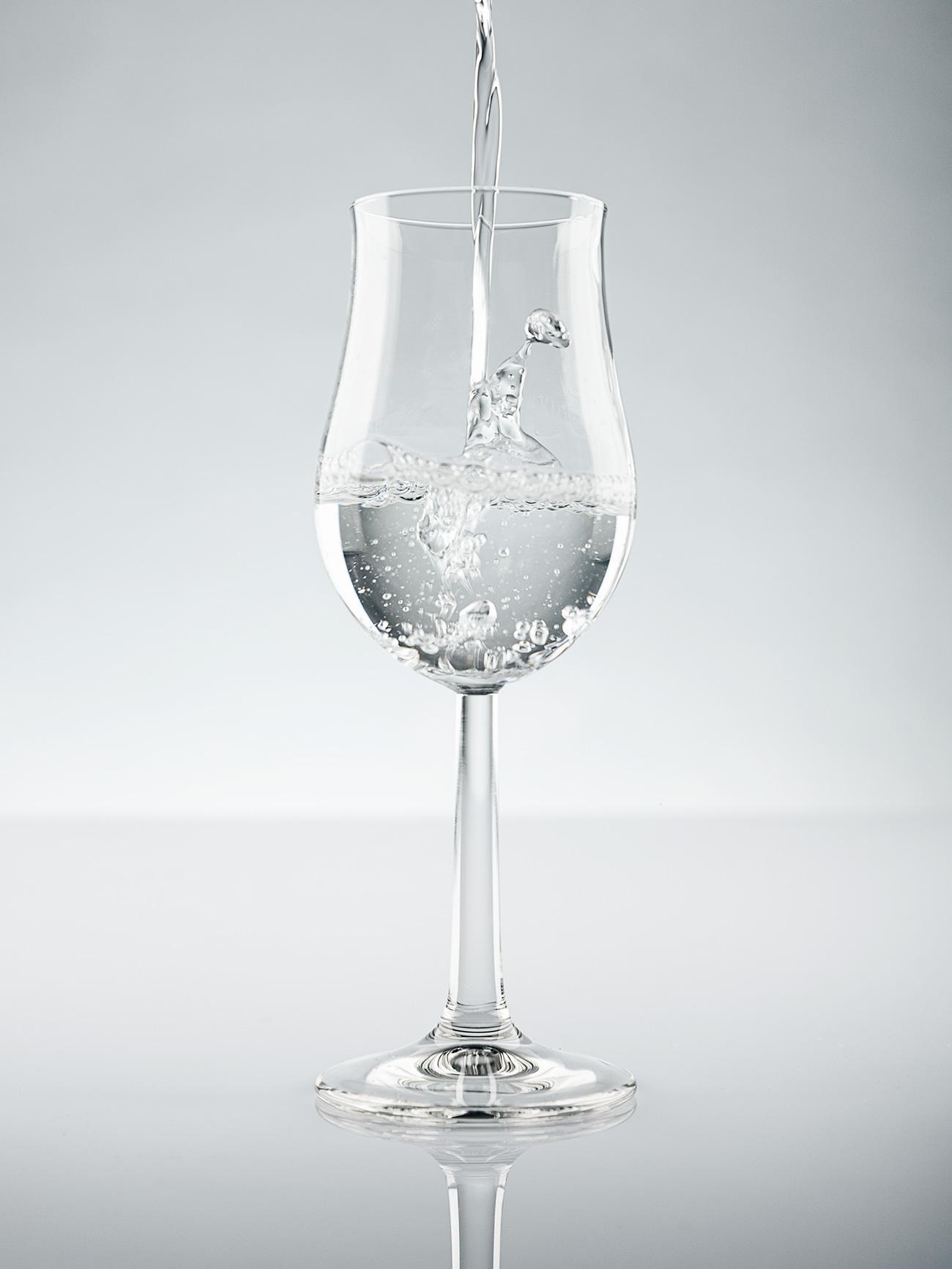Ein Degustationsglas mit klarem Rum von Ron Elba. Es wird gerade befüllt.
